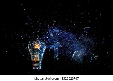 Сosmic explosion of burning light bulb with flying splinters of broken glass and smoke on isolate black background. Сoncept of creative art of starry sky, cosmos,  universe and the big bang theory.
