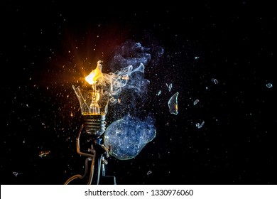 Сosmic explosion of burning light bulb with flying splinters of broken glass and smoke on isolate black background. Сoncept of creative art of starry sky, cosmos,  universe