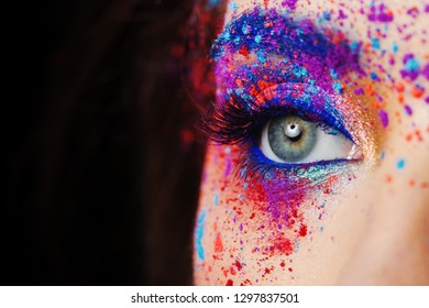 explosion of color, multi-colored shadows scattered on the eyelids. Colored Smokey eyes and blue eyebrows. Fashion portrait close up