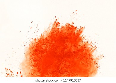 Explosion of colored powder isolated on white background. Power or clouds splatted. Freez motion of orange dust exploding.