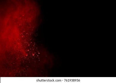 Explosion of red powder on black background