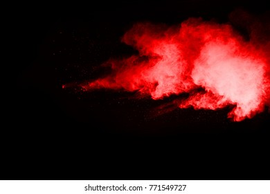 Explosion of red powder on black background.