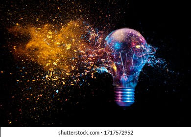 Explosion einer herkömmlichen Glühbirne. Aufnahme in hoher Geschwindigkeit, zum genauen Zeitpunkt des Aufpralls. Farbige Lichter und schwarzer Hintergrund. Konzept der Kreativität und Fragilität.