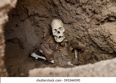 Exposed human skeleton and skull in a burial mound in the Andes still partly embedded in the hardened clay and rock viewed through a hole in the wall of the chamber