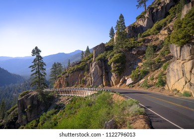 Exposed mountainside road curve - afternoon on Highway 108, California