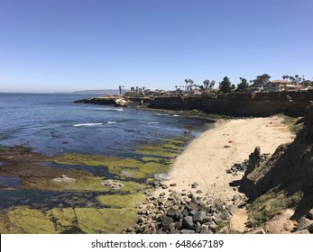 An exposed reef contrasts with a sunny beach at Sunset Cliffs in San Diego, California.