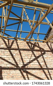 Exposed roof trusses and unfinished brick walls in new building.