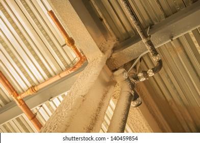 exposed underside of steel floor or roof deck with utilities and spray-on fireproofing