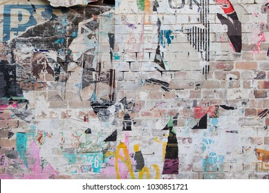 exposed weathered brick wall with torn street posters
