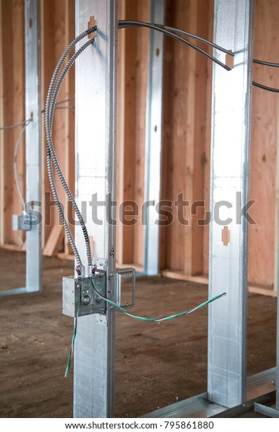 exposed wiring for an electrical power outlet box, attached to an aluminum  framing post,