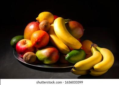 Exposition of fresh organic fruits on plate, orange, mango, banana, apple, kiwi, lemon on black background. Nature and healthy fruit.