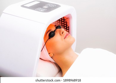 Express facial treatment with led therapy. Beautiful girl on a light therapy procedure. LED lamp with red light.