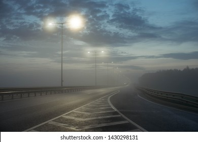 Express Motorway. Way free. The road goes away, wet asphalt after rain, fog dissipates. Late spring evening at sunset.