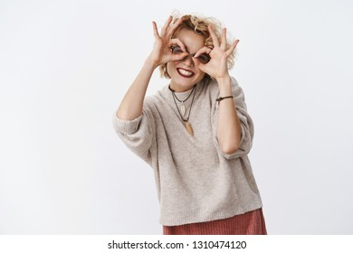 Express your happiness. Carefree funny and beautiful joyful girl with short blond hair and dark lipstic smiling broadly showing glasses on eyes with circles fooling around and feeling playful