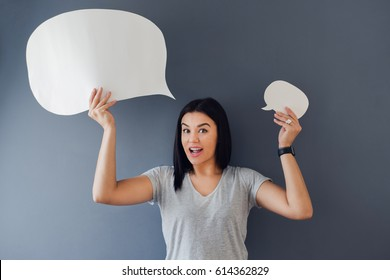 Express yourself!. Young woman holding two empty thought bubbles above he head