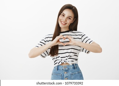 Expressing care and love. Portrait of bright attractive feminine woman in casual spring outfit, showing heart gesture over chest and smiling broadly, confessing in sympathy over white background