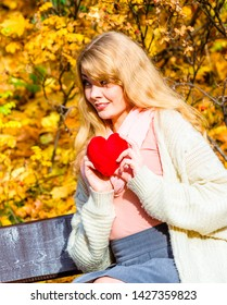 Expressing feelings and affection. Confess love with romantic gesture. Young woman sit on bench in park holding plush heart smiling and sharing good emotions.