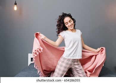 Expressing true positive emotions of young excited brunette woman in pajamas having fun with pink blanket on gray wall background. Relaxing at home comfort in modern apartment