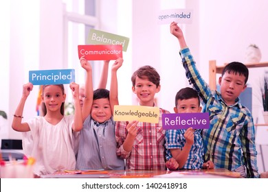 Expressing yourself. Smiling children holding up colorful sheets of paper with English words describing their personalities.
