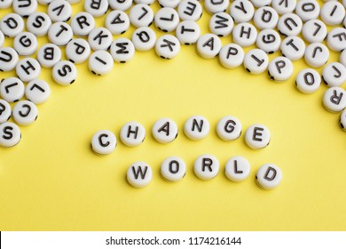 The expression CHANGE WORLD made of white plastic blocks on yellow background with many letters on the top
