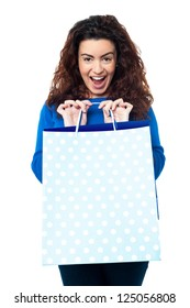 Expression of an excited woman displaying her shopping bags to the camera.