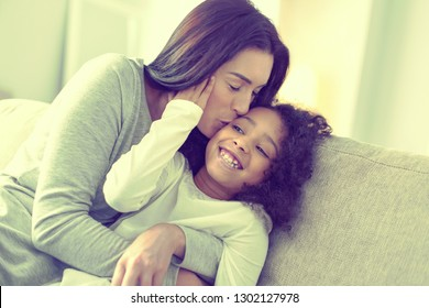 Expression of love. Happy young mom giving her little daughter a loving peck.