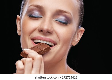 expression portrait of beautiful happy brunette girl tasting chocolate on black