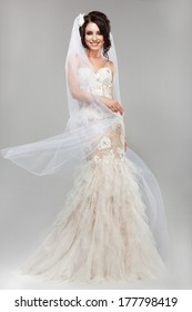 Expression. Positive Emotions. Gorgeous Smiling Bride in Windy Wedding Dress