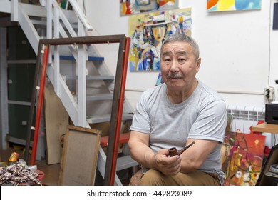 Expressionist artist in the interior of his art studio among his paintings