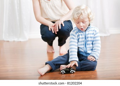 Expressive baby boy playing with a toy car with mother in the background