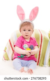 Expressive baby girl with fluffy bunny ears holding Easter egg