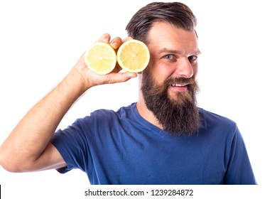 Expressive bearded man holding two halfs of a lemon over white background.