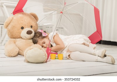 Expressive beautiful little girl having a tea party with her teddy bear, sitting under umbrella, indoor.