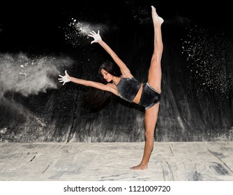 Expressive beautiful teenage female contemporary ballet dancing on stage with black background and white flour