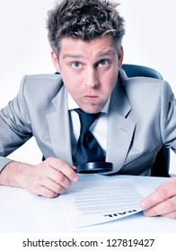 Expressive businessman with magnifying glass analyze contract