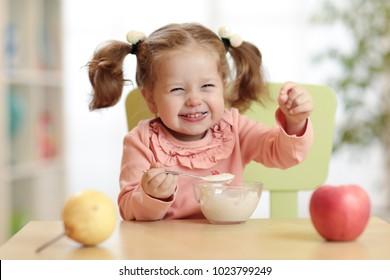 Expressive child girl eating healthy breakfast at kindergarten.