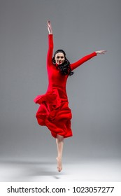 Expressive dance position of beautiful sexy happy smiling brunette ballerina in red evening dress looking at camera, copy-space. Grey background