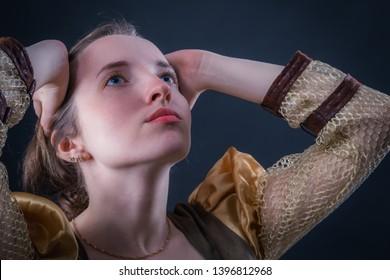 Expressive emotionally praying princess girl in a vintage dress. Dark background