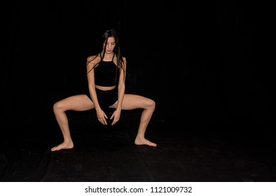 Expressive female contemporary ballet dancer, dancing  on stage with a black background.