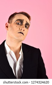 Expressive glance. Mime artist. Man with mime makeup. Mime with face paint. Theatre actor miming. Stage actor playing. Theatrical performance art and pantomime. Drama or tragedian performer.