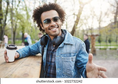 Expressive handsome dark-skinned male with afro haircut in glasses, denim coat and headphones, leaning on table while drinking coffee in park, gesturing as if telling story. Guy waits for his order