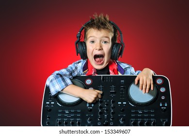 Expressive little boy DJ in headphones mixing up some party music.