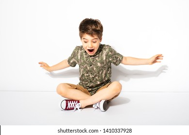 expressive little boy posing while sitting down on white background