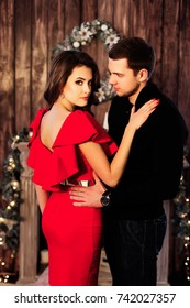 Expressive look of hot woman in red dress embraced by her husband standing in a room decorated for christmas