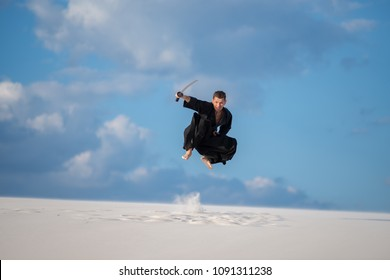 Expressive man, in traditional clothes jumps with a Japanese sword, katana, in the desert during sunset -  practice Japanese martial arts outdoor.