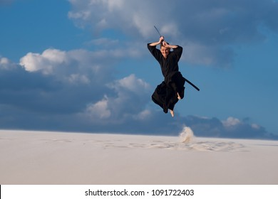 Expressive man, in traditional Japanese clothes is jumping with katana during training martial arts in desert at sunset - fierce samurai on the cloudy sky background.