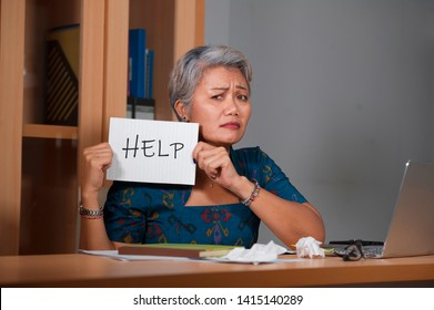 expressive portrait of attractive stressed and overworked Asian woman working at office laptop computer desk in stress feeling frustrated and helpless asking for help holding notepad