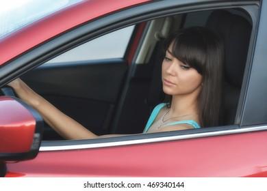 Expressive portrait of a beautiful cute girl sitting in red car