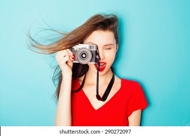 Expressive portrait of a beautiful young brunette woman in a red dress in the studio on a blue background with a camera in his hands