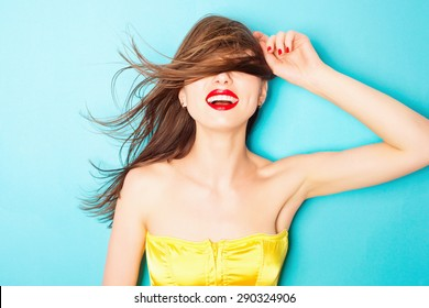 Expressive portrait of a beautiful young brunette woman in the studio on a blue background, the concept of beauty